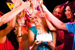 portrait of joyful girl holding birthday cake surrounded by her friends with flu - stock photo