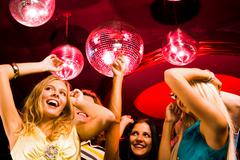pretty girls moving at disco while spending time in night club - stock photo