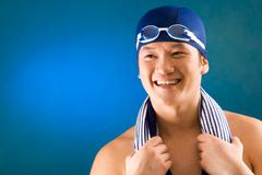 Portrait of happy sportsman in swimming cap and goggles over blue background Stock Photos