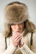 portrait of cold man in fur hat and knitted sweater warming up his hands - stock photo