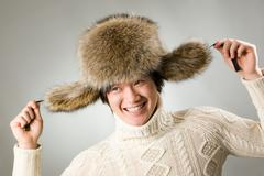 Portrait of happy man in warm fur hat and white sweater having fun Stock Photos