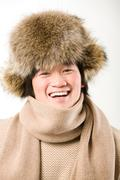 Portrait of happy man in warm fur hat and white sweater laughing Stock Photos