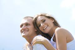 laughing female embracing her husband on background of blue sky - stock photo
