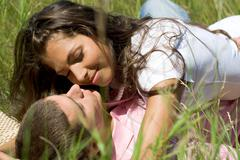 Photo of tender girl embracing her boyfriend while lying on grass Stock Photos