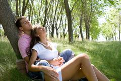 Image of amorous couple having peaceful rest on green grass of park together Stock Photos