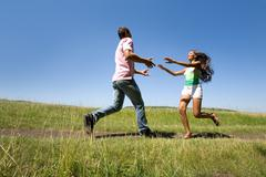 photo of young man and woman running to each other outdoors - stock photo