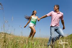 photo of young man and woman holding each other by hands and running outdoors - stock photo