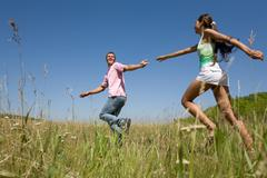 attractive dates having fun while running down green field during weekend - stock photo