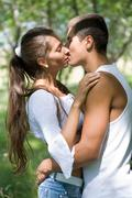photo of pretty girl and her boyfriend kissing outdoors - stock photo