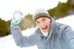 image of attractive young man with snowball ready to throw it - stock photo