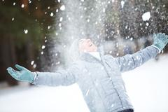 portrait of cute guy taking pleasure on snowy winter day - stock photo