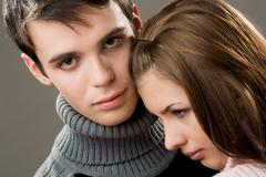 Handsome guy looking at camera with lovely girlfriend by his side Stock Photos