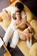 over view of happy female on sofa being embraced by her boyfriend - stock photo