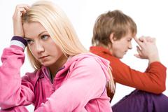 Image of sad girl with confused guy at background after having an argument Stock Photos