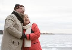 Loving aged couple standing near lake and embracing each other Stock Photos