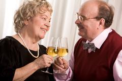 portrait of senior couple celebrating their golden wedding with champagne - stock photo