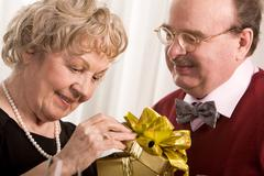 image of aged woman opening giftbox with her husband near by - stock photo