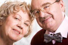 two smart elderly people looking at camera during their jubilee - stock photo