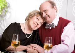 photo of devoted husband and wife sitting next to each other at table in restaur - stock photo