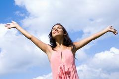 Portrait of happy girl praising god with her eyes shut and raised arms on backgr Stock Photos