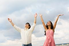 Portrait of happy couple standing with raised arms on background of cloudy sky Stock Photos