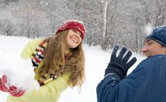 portrait of woman holding snow with man near by - stock photo