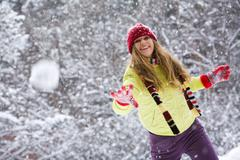 Moment of play: young woman flinging the snowball Stock Photos