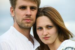 portrait of attractive couple looking at camera outdoor - stock photo