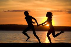 Silhouettes of happy couple having fun on seashore at sunset Stock Photos