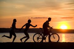 silhouettes of happy couple running behind man riding bicycle on seashore at sun - stock photo