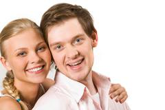 close-up of happy couple looking at camera close to each other - stock photo