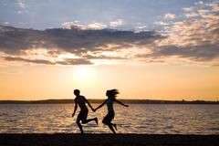 Silhouettes of happy couple running on seashore during summer vacations Stock Photos