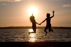 Silhouettes of happy couple jumping on background of lake at sunset Stock Photos