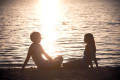 Photo of serene couple sitting on the seashore and talking at sunset Stock Photos