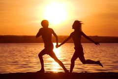 Stock Photo of silhouettes of happy couple running down seashore at sunset