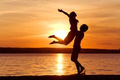 Figures of happy guy holding his girlfriend while the latter raising her arms at Stock Photos