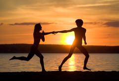 Silhouettes of happy couple running down seashore at sunset Stock Photos