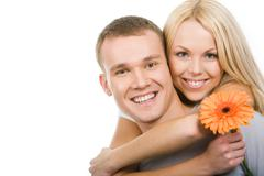Portrait of attractive young girl with herbera embracing her boyfriend while bot Stock Photos
