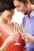 Portrait of happy couple with champagne flutes looking at each other Stock Photos