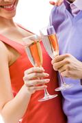Close-up of couple with champagne flutes celebrating holiday Stock Photos