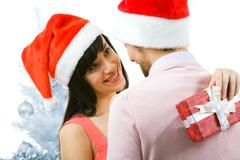 portrait of happy woman looking at man with smile and keeping giftbox behind his - stock photo