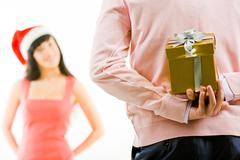 rear view of man holding giftbox in hand on background of intrigued female - stock photo