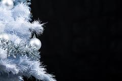 part of festive new year tree decorated with silver garlands and toy balls over - stock photo