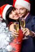Image of happy couple stretching champagne flutes with silver tree at foreground Stock Photos
