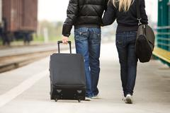Stock Photo of rear view of couple walking down train station with their baggage