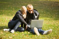 Photo of pretty girl and handsome guy sitting on grass and looking at laptop mon Stock Photos