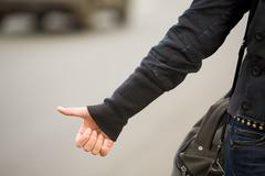 close-up of female hand gesture of hitchhiking outside - stock photo