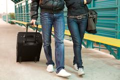 legs of couple walking down train station with their baggage - stock photo