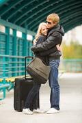 photo of pretty girl and her boyfriend embracing on station during seeing off - stock photo