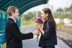 photo of happy girl with aster bouquet smiling to handsome guy outside - stock photo